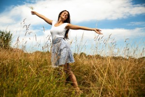 Sunrise Holostic: Attractive happy woman joying in beautiful summer day.